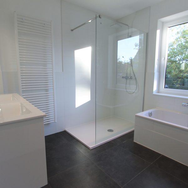 Witte badkamer met inloopdouche en zwarte tegels.