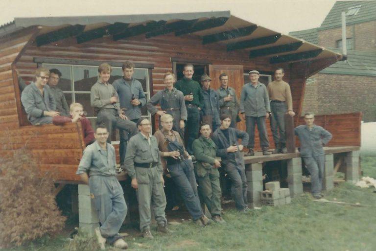 Groepsfoto van mannen die een huis bouwen