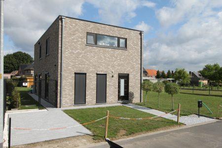 Simplistische grijze Q-Big woning van Quackels Woningbouw, met verticale en horizontale raampartijen.