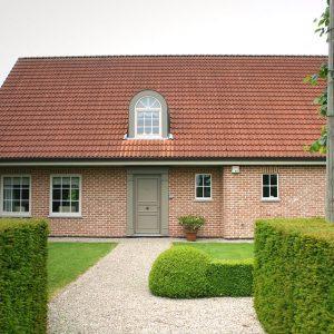 Eenvoudige, klassieke woning met bruine voordeur.
