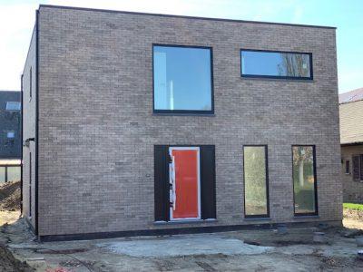 Simplistische grijze Q-big woning met mooie raampartijen, gebouwd als investeringsproject.