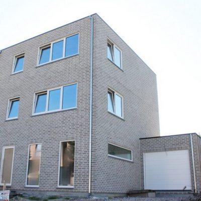 Grijs appartementsgebouw, gebouwd door Quackels Woningbouw