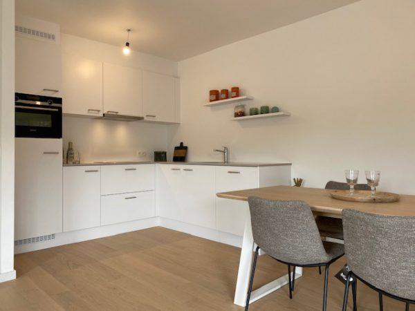 Hoekkeuken met houten tafel en grijze stoelen in Quackels huis